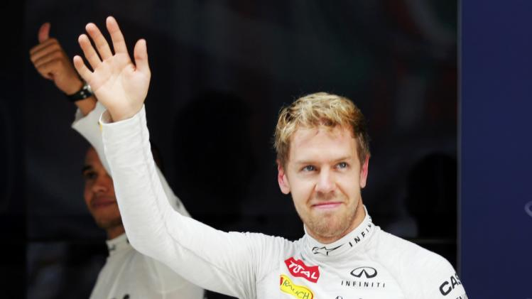 Red Bull Formula One driver Vettel and Mercedes Formula One driver Hamilton gesture after the qualifying session of the Indian F1 Grand Prix at the Buddh International Circuit in Greater Noida