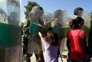 A Palestinian girl pushes an Israeli soldier during a weekly protest against Israel's controversial separation barrier in the West Bank village of Maasarah, near Bethlehem. Israel has long feared that if the Palestinians won the rank of a UN non-member state, they could pursue the Jewish state for war crimes at the International Criminal Court -- particularly over ettlements