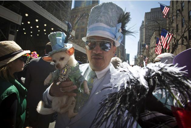 A man holds his dog as they participate in the annual Easter Bonnet Parade in New York