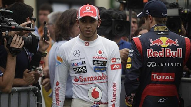 McLaren Formula One driver Lewis Hamilton of Britain (L) walks past Red Bull driver Sebastian Vettel of Germany,