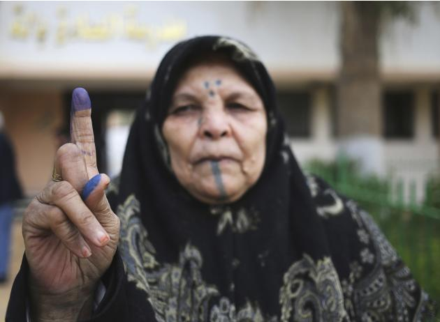 Woman holds up her ink-stained finger after casting her ballot in a municipal election in Benghazi
