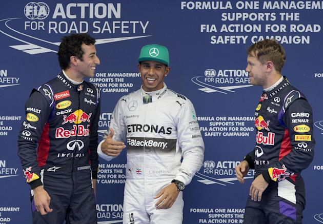 Red Bull Racing driver Daniel Ricciardo of Australia, left, Mercedes driver Lewis Hamilton of Britain, center, and Red Bull Racing driver Sebastian Vettel of Germany, right, chat after the qualifying