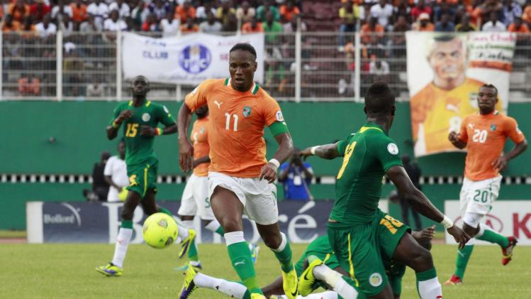 Ivory Coast's Didier Drogba controls the ball against Senegal's players during their 2014 World Cup qualifying soccer match in Abidjan