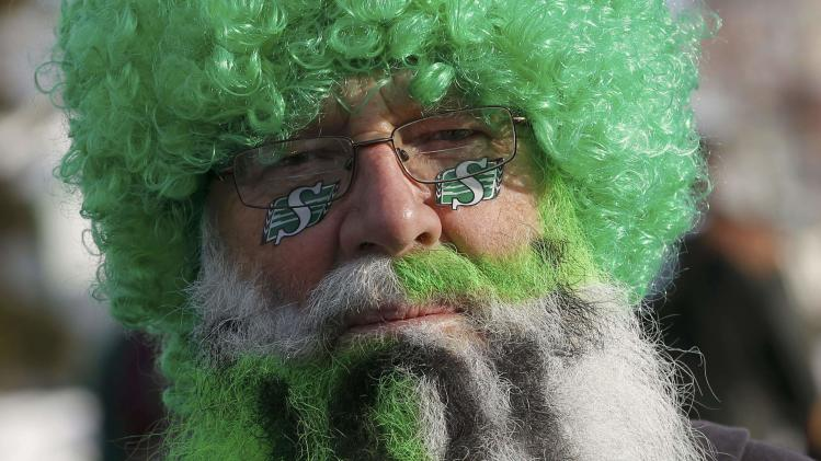 A Saskatchewan Roughrider fan dressed up in a wig and painted beard gets ready for the 101st Grey Cup game between the Saskatchewan Roughriders and the Hamilton Tiger Cats in Regina