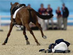 Woojin Hwang, of Korea, lays on the ground after getting bucked off his horse Shearwater Oscar, in the equestrian show jumping stage of the men's mode