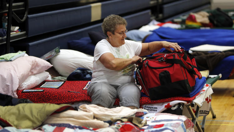 Sherri Kaderka looks in her bag at the American Red Cross shelter in Monument, Colo., for evacuees from the nearby Black Forest wildfire on Friday, June 14, 2013. Nearly 4,000 people are still evacuated from the fire that broke out on Tuesday. (AP Photo/Ed Andrieski)