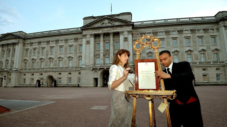 The Queen's Press Secretary Ailsa Anderson, with Badar Azim, a footman, places an official document to announce the birth of a baby boy, at 4.24pm to the Duke and Duchess of Cambridge at St Mary's Hospital, in the forecourt of Buckingham Palace in London Monday July 22, 2013. The child is now third in line to the British throne. (AP Photo/John Stillwell, Pool)