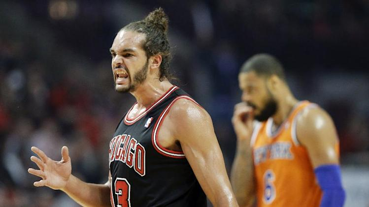Chicago Bulls center Joakim Noah, left, reacts after Derrick Rose scored a basket as New York Knicks center Tyson Chandler is at right during the first half of an NBA basketball game in Chicago, Thursday, Oct. 31, 2013