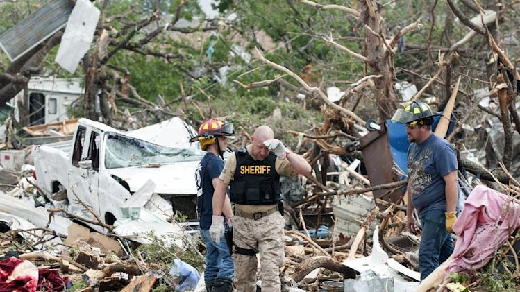 Emergency personnel look through debris on near Granbury, Texas  on Thursday, May 16, 2013. Ten tornadoes touched down in several small communities in Texas overnight, leaving at least six people dead, dozens injured and hundreds homeless. Emergency responders were still searching for missing people Thursday afternoon. (AP Photo/Rex C. Curry)