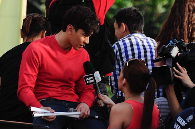 "Enchong Dee star of the MMFF 2012 entry ""The Strangers"" is being interviewed by a journalist during the 2012 Metro Manila Film Festival Parade of Stars on 23 December 2012.(Angela Galia/NPPA Images)"