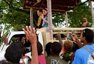 Britain's Prince William and his wife Catherine, the Duchess of Cambridge, wave to locals as they leave the airport aboard a truck decorated as a canoe, in Honiara on September 16. Queen Elizabeth, William's grandmother, is head of state in the Solomons and Tuvalu, both of which are members of the Commonwealth, as are Singapore and Malaysia