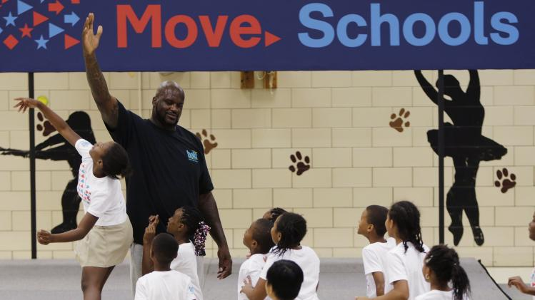 Former NBA star Shaquille O'Neal high fives school children at a back-to-school event in Washington