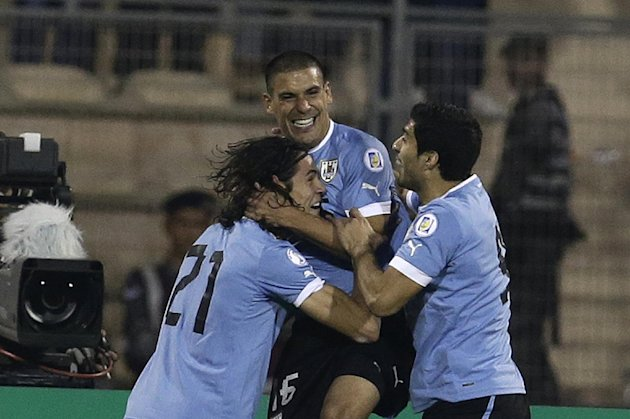 Uruguay's Maximiliano Pereira, right, celebrates with his teammates Edinson Cavani, left, and Luis Suarez after scoring the opening goal against Jordan during the World Cup play off first leg soccer match between Jordan and Uruguay at Amman International stadium in Amman, Jordan, Wednesday, Nov. 13, 2013. (AP Photo/Hassan Ammar)