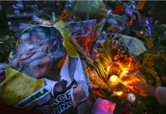 A mourner places a candle on a pile of flowers and photos of Mandela during a homage outside the Houghton home of the late former South African President Nelson Mandela in Johannesburg