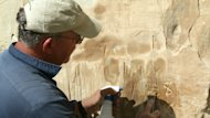 Jannie Loubser, a renowned expert on rock art remediation, works on reclaiming some of the aboriginal etchings at Writing-on-Stone Provincial Park.