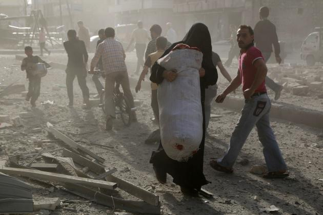 Woman carries a sack full of belongings at a site hit by what activists said were barrel bombs dropped by forces loyal to Syria's President Assad in Aleppo
