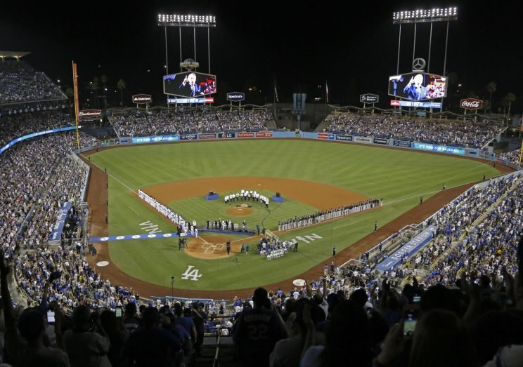 Both teams stand on the baselines as the members of the Los Angeles Philharmonic, under the direction of famed composer John Williams, prepare to play the national anthem as Los Angeles Dodgers Hall of Fame broadcaster Vin Scully is honored in a ceremony before a baseball game against the Colorado Rockies at Dodger Stadium Friday, Sept. 23, 2016. (AP Photo/Reed Saxon)