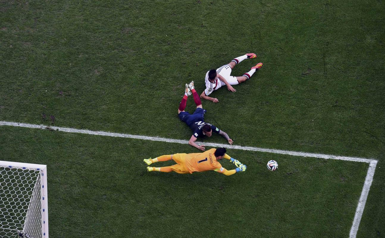 France's Lloris dives for the ball next to Debuchy and Germany's Klose during their 2014 World Cup quarter-finals at the Maracana stadium in...