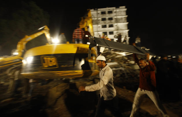 Rescue workers carry a stretcher near the  site where  a residential building collapsed in Thane, Mumbai, India, Thursday, April 4, 2013. At least 6 persons were killed and 40 were injured when an und