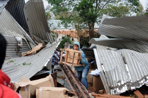 A worker at a clothes factory destroyed by a storm tries to salvage whatever is left, in Mariano Alonso Roque, on September 19, 2012. Fierce storms packing 140-kilometer (87-mile) an hour winds tore across the heart of South America on Wednesday, killing five people in Paraguay, two in Uruguay and two in Bolivia.