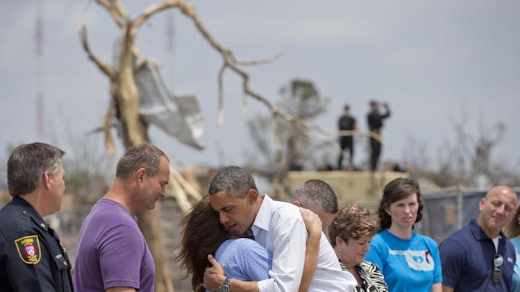 President Barack Obama embraces a school official as he views the devastation of the Plaza Towers Elementary School, Sunday, May 26, 2013, in Moore, Okla., caused by a tornado and severe weather last week. (AP Photo/Carolyn Kaster)