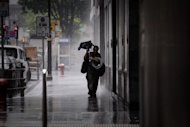 A man battles with his broken umbrella against heavy winds in Hong Kong on August 13, 2013. Hong Kong battened down Wednesday as Severe Typhoon Utor forced the closure of the financial market and disrupted hundreds of flights