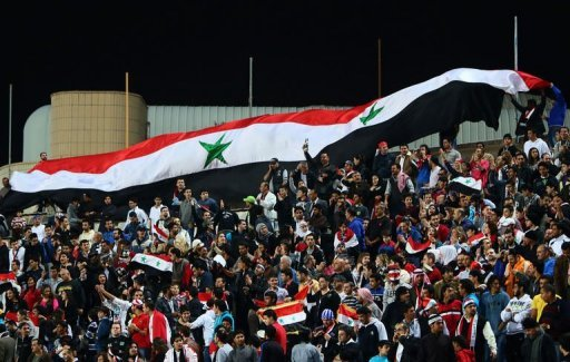 Syrian football fans wave a giant national flag during Syria's final football match against Iraq in the 7th West Asia Football Federation championship in Kuwait City, on December 20, 2012. Syria won 1-0