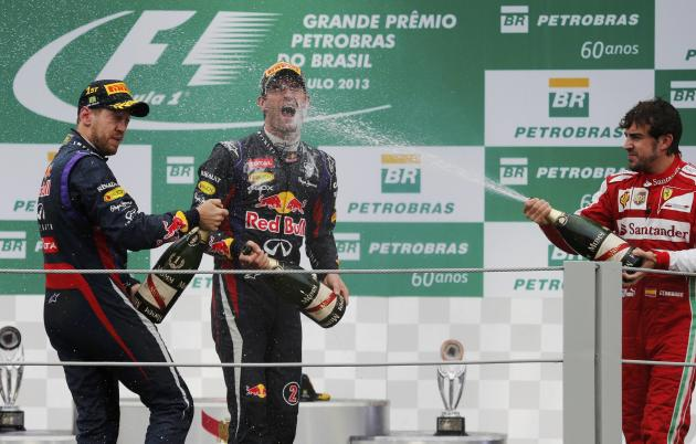 Sebastian Vettel of Germany, Mark Webber of Australia and Fernando Alonso of Spain spray champagne as they celebrate on the podium after the Brazilian F1 Grand Prix at the Interlagos circuit in Sao Pa