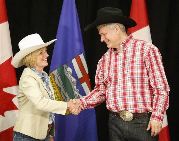 Alberta Premier Rachel Notley, left, greets Prime Minister Stephen Harper with a handshake in Calgary, Alta., on Monday, July 6, 2015. THE CANADIAN PRESS/Jeff McIntosh