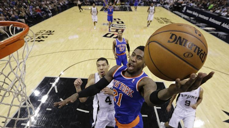 New York Knicks' Iman Shumpert (21) scores in front of San Antonio Spurs' Danny Green (4) during the first half of an NBA basketball game, Thursday, Jan. 2, 2014, in San Antonio