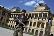 A security officer stand guard outside the Darulaman Palace in Kabul. The National Museum of Afghanistan is overlooked by living history represented by the ruins of the neoclassical Darulaman Palace on a neighbouring hill -- also a victim of war