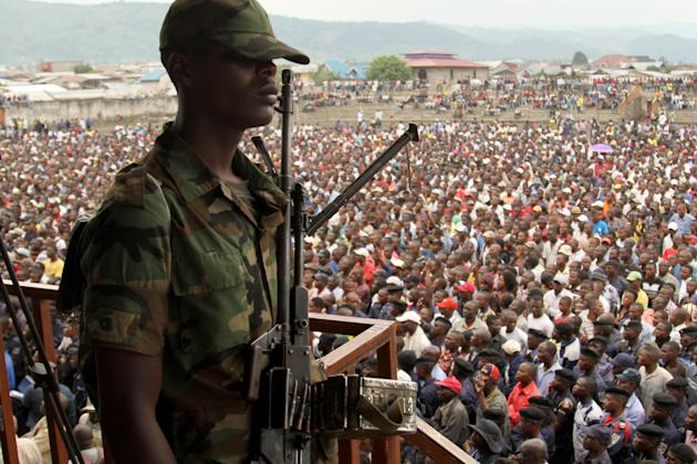 A soldier from the M23 rebel group looks on as thousands of Congolese people listen during an M23 rally, in Goma, eastern Congo, Wednesday, Nov. 21, 2012. Thousands of Congolese soldiers and policemen