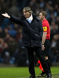 Manchester City's manager Roberto Mancini gestures to his players during their Premiership football match against Reading at The Etihad stadium in Manchester, northwest of England on December 22, 2012. Mancini admits Manchester City's bid to catch Premier League leaders Manchester United may prove a heart-stopping affair after the champions' dramatic 1-0 win against Reading