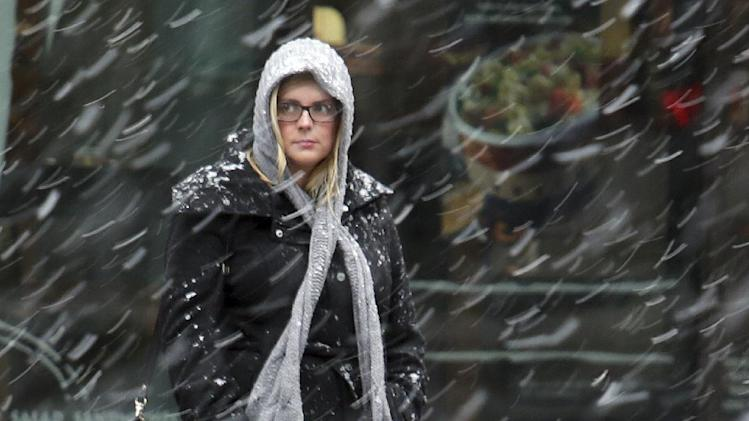 A morning commuter, bundled against the cold, watches the snow begin to fall in Washington early Wednesday, March 6, 2013. The Mid-Atlantic region is expected to get 6 to 10 inches of snow. (AP Photo/J. David Ake)