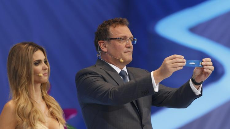 "Valcke holds up the slip showing ""Algeria"" during the draw for the 2014 World Cup in Sao Joao da Mata"