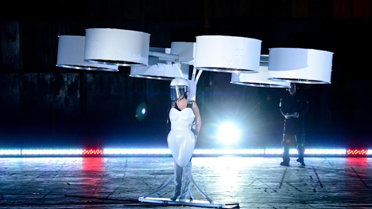 "Lady Gaga demonstrates the Volantis transport prototype ""flying dress"" designed by TechHaus - Studio XO during the ARTPOP album release and artRave event at the Brooklyn Navy Yard on Sunday, Nov. 10, 2013 in New York City. (Photo by Evan Agostini/Invision/AP)"