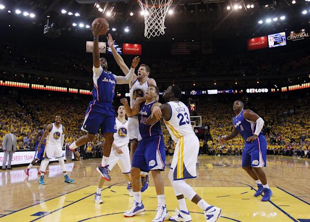 Los Angeles Clippers' Chris Paul, left, goes up for a layup past Golden State Warriors' David Lee (10), teammate Blake Griffin (32) and the Warriors' Draymond Green (23) during the second