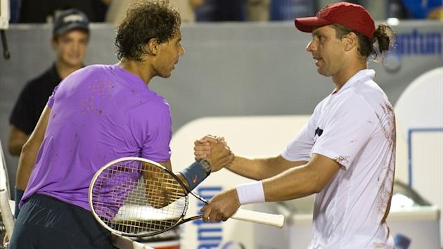 Argentine Horacio Zeballos (R) shakes hands with Spanish tennis player Rafael Nadal after beating him at the ATP Vina del Mar tournament