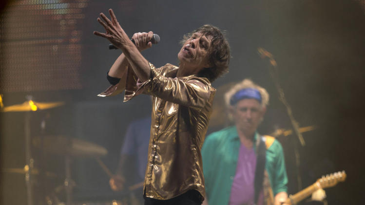 Mick Jagger of British band the Rolling Stones performs on the Pyramid main stage at Glastonbury, England, Saturday, June 29, 2013. Thousands of music fans have arrived for the festival to see headliners, Arctic Monkeys, Mumford and Sons and the Rolling Stones.(Photo by Joel Ryan/Invision/AP)