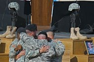 US soldiers comfort each other at the Fallen Soldier Memorial at Fort Hood on November 10, 2009. The US Army psychiatrist accused of opening fire on fellow soldiers in the deadliest such incident at a US military base took charge of his own defense as his high-profile trial got underway