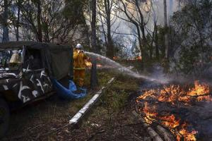 Rural Fire Service firefighter sprays water onto a small fire burning near a home in western Sydney