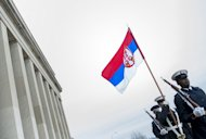 Guards are seen marching with the Serbian flag after the arrival of Serbia's Minister of Defense Aleksandar Vucic during a honor cordon at the Pentagon, on December 6, in Washington, DC