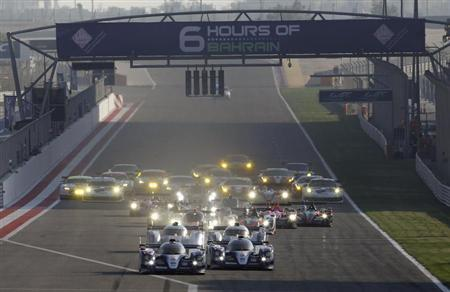Race cars compete during the start of the final race of the 2013 WEC Six Hours of Bahrain at the BIC in Sakhir