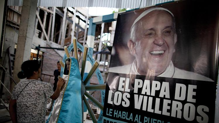 "A woman touches a religious figure beside a banner of Pope Francis reading in Spanish, ""The Pope of the people of the slum"" as she attends a mass in his honor at the 1-11-14 slum's church in Buenos Aires, Argentina, Thursday, March 13, 2014. On the day of the first anniversary of the Pope's election, people from the 1-11-14 slum gather at their church to watch an interview that Pope Francis gave recently from his residence at the Vatican to FM Bajo Flores, a community radio station that broadcasts from the slum. (AP Photo/Natacha Pisarenko)"