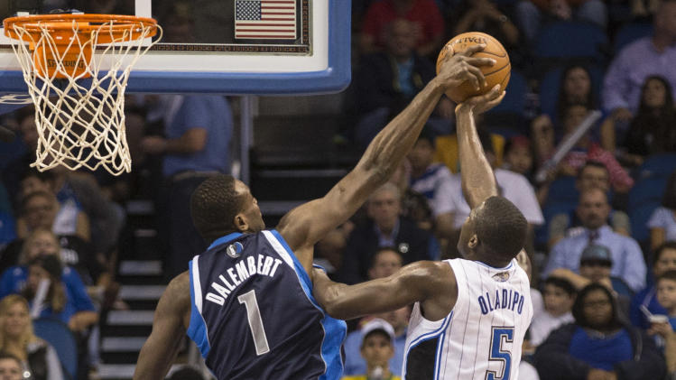 Dallas Mavericks' Samuel Dalembert, left, blocks Orlando Magic's Victor Oladipo's shot during the second half of an NBA basketball game in Orlando, Fla., Saturday, Nov. 16, 2013