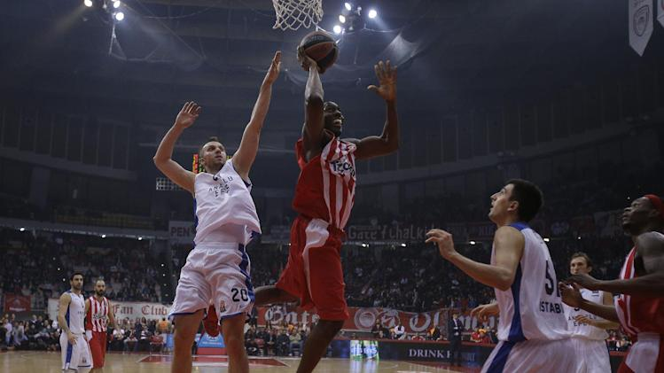 Olympiakos' Bryant Dunston scores as Anadolou Efes' Dusko Savanovic, 20, tries to stop him during their Euroleague basketball match of Top 16 in the port of Piraeus, near Athens, Thursday, Feb. 13, 2014