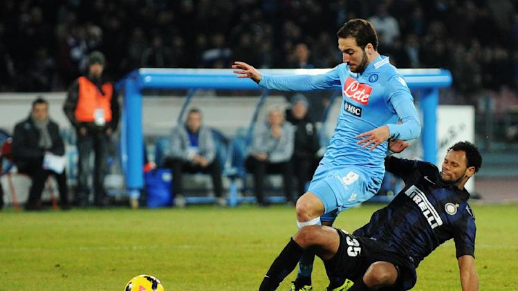 Napoli's Gonzalo Higuain, left, vies for the ball with Inter's Rolando during a Serie A soccer match between Napoli and Inter Milan, at the San Paolo stadium in Naples, Italy, Sunday, Dec, 15, 2013