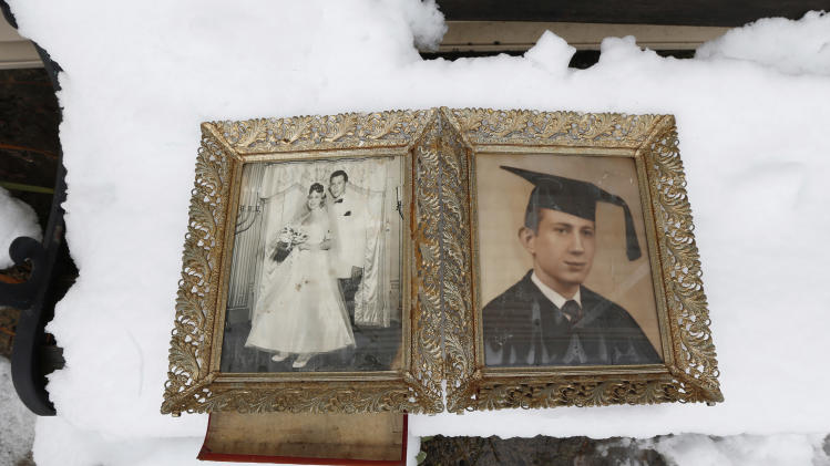 Photographs of Elliott Miller's wedding day and graduation lay on a snow covered bench as Jeanene Miller tries to dry out the pictures of her in-laws which were damaged during floods caused by Superstorm Sandy, Thursday, Nov. 8, 2012, in Point Pleasant, N.J.  The New York-New Jersey region woke up to wet snow and more power outages Thursday after the nor'easter pushed back efforts to recover from Superstorm Sandy, that left millions powerless and dozens dead last week. (AP Photo/Julio Cortez)