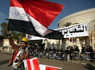 "A street vendor waves th Egyptian flag outside the presidential palace guarded by riot police in Cairo. Egypt's powerful military has demanded the Islamist-led government and political foes start dialogue and warned it will not permit events to take a ""disastrous"" turn"