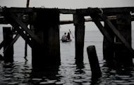 Fishermen paddle their boat in the Philippines in March 2012. Philippine emergency workers Saturday rescued 30 fishermen whose boat was left drifting in rough seas amid the country's first tropical storm of the year, which also left hundreds of travellers stranded